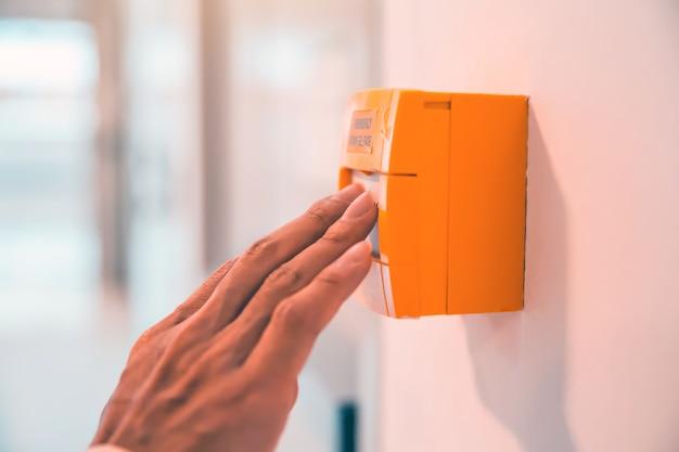 Close-up hand is druk op de noodschakelaar voor deuropener bij de nooduitgang in het gebouw