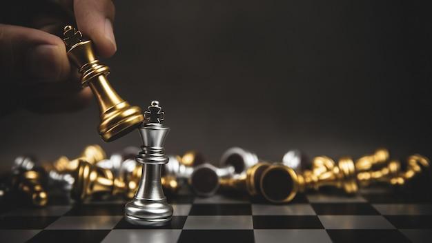 Close-up hand kies gouden schaken om te vechten met zilveren schaakteam op schaakbord