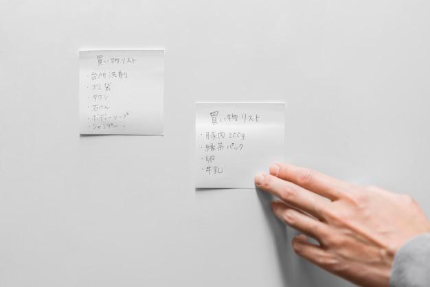 Close-up hand kleverige nota aan te raken