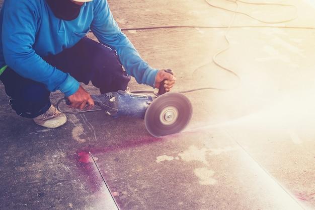 Close-up hand man snijden betonnen vloer met machine.