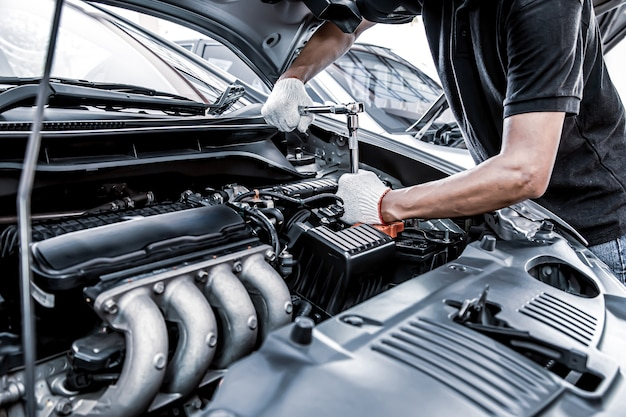 Close-up hand met behulp van de sleutel om de motor van een auto te repareren.