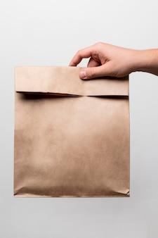Close-up hand met papieren zak