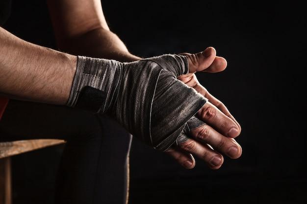 Close-up hand met verband van gespierde man kickboksen opleiding op zwart