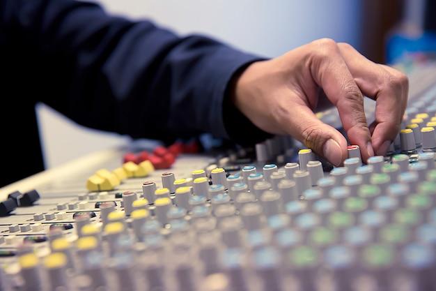 Close-up hand pas het volume aan op de geluidsmixer.