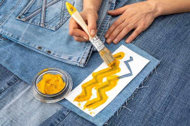 Close-up hand schilderij jeans