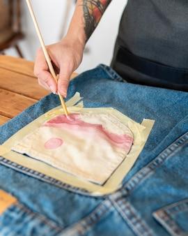 Close-up hand schilderij op kledingstuk