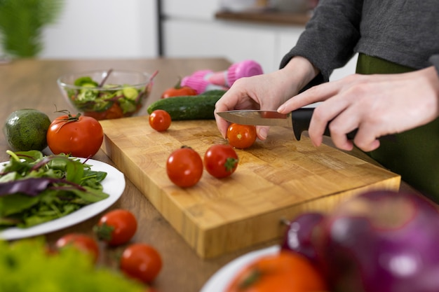 Close-up hand snijden tomaat op een houten bord