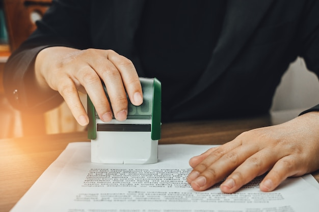 Close-up hand stempelen van zakenvrouw voor het ondertekenen van goedkeuring op documenten