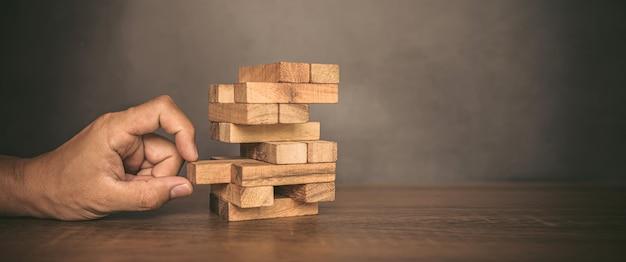 Close-up hand trekken houten blok van andere het hout blok gestapeld in torenvorm