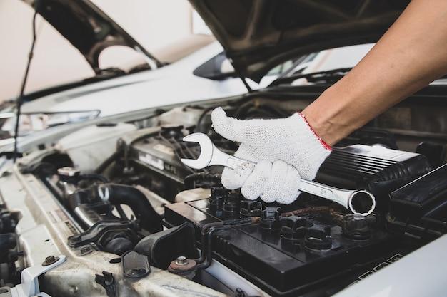 Close-up hand van automonteur gebruikt moersleutel om de motor van een auto te repareren