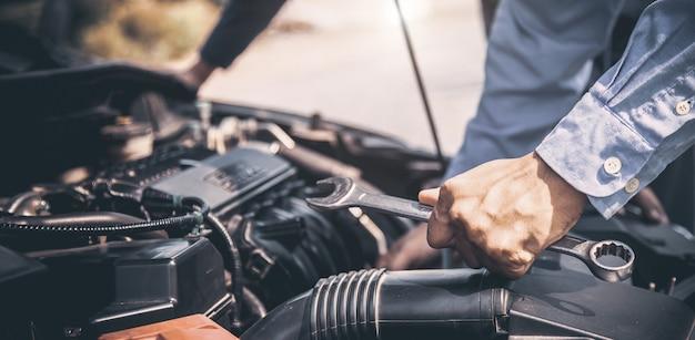 Close-up hand van automonteur met behulp van moersleutel om de motor van een auto te repareren.