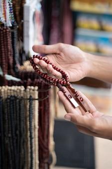 Close-up hand van aziatische moslim man winkelen voor islamitische kralen