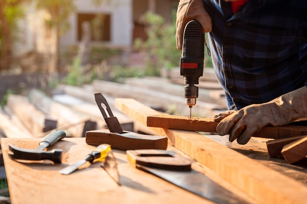 Close-up hand van carpenter boort hout een gat met een elektrische boor.