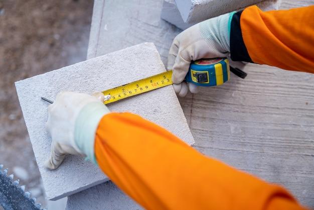 Close-up hand van de tegelzetter gebruikte een meetlint om de grootte van de lichtgewicht stenen op de bouwplaats te meten.