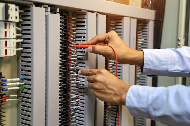 Close-up hand van elektrotechniek met behulp van meten om elektriciteit te controleren.