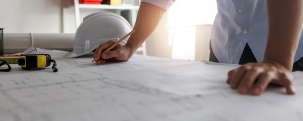 Close-up hand van ingenieur tekenen en ontwerpen op blauwdruk op tafel, architect werken en creëren in kantoor