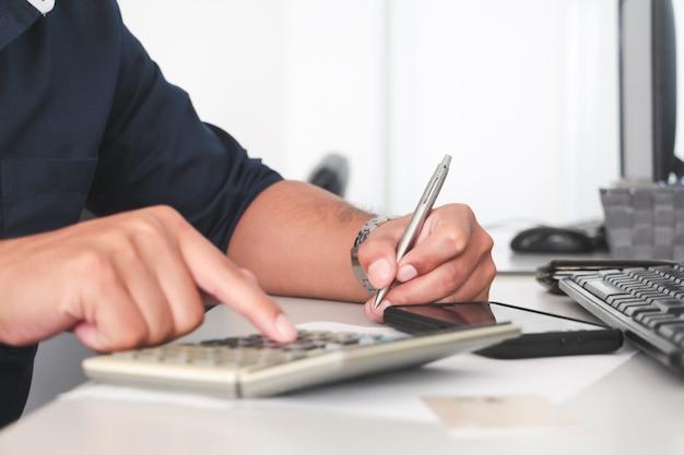 Close-up hand van man schrijven met pen op papier en vinger aanraking rekenmachine. werkend kantoorconcept. werk concept. digitaal betalingsconcept. account of financieel. aankoop of koper concept.