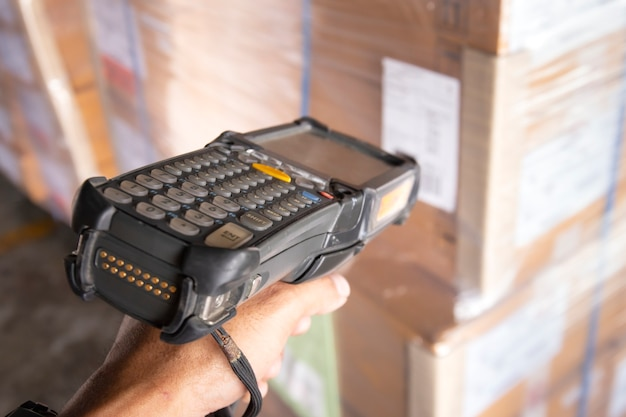 Close-up, hand van werknemer die streepjescodescanner houdt die ladingsdozen scannen.
