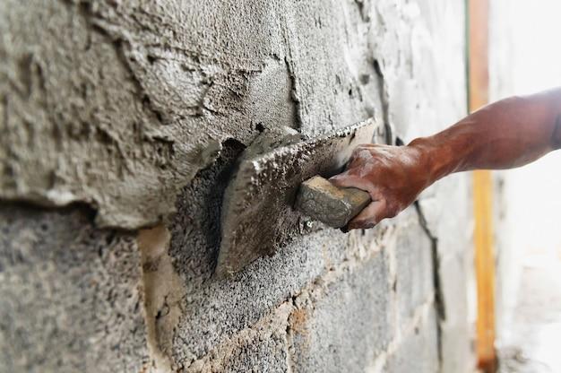 Close-up hand van werknemer stukadoors cement op muur in bouwplaats