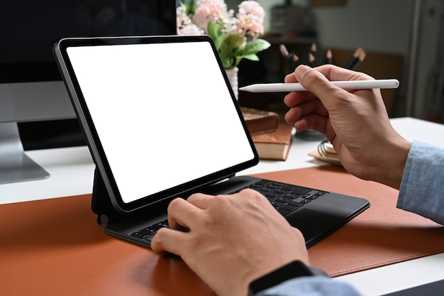 Close-up hand van zakenman bedrijf stylus pen wijzend op het scherm van de computertablet