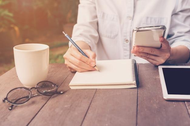 Close-up hand vrouw schrijven notitieboekje en telefoon in de koffiewinkel met vintage toned.