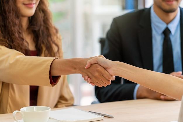 Close-up handdruk bij interview tussen jonge aziatische vrouw en twee manager