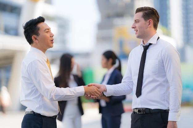Close-up, handdruk van twee zakenlieden op de achtergrond van modern kantoor, partnerschap concept, handen schudden om een deal te sluiten