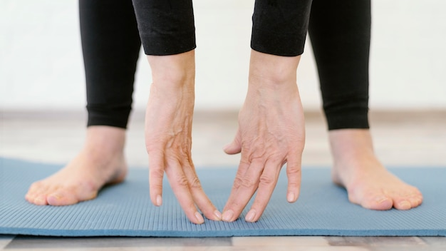 Close-up handen aanraken yogamat