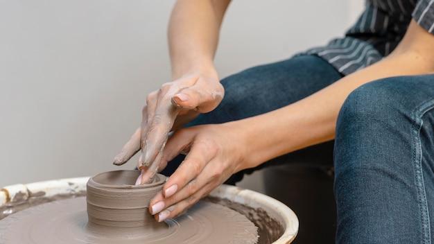 Close-up handen aardewerk doen