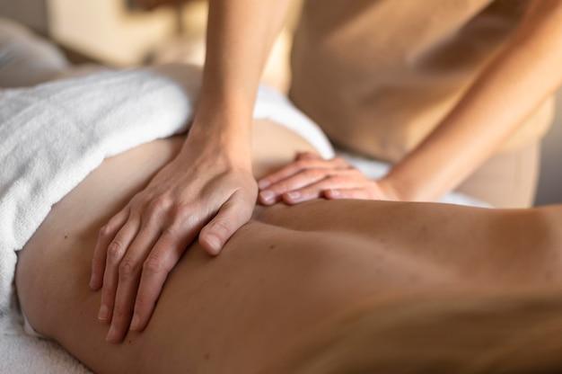 Close-up handen die de rug van de persoon masseren