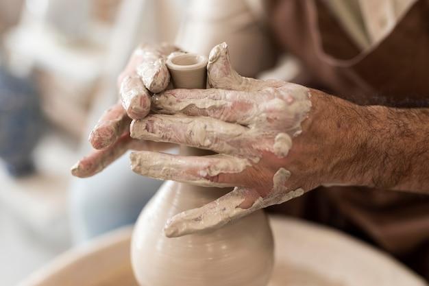 Close-up handen doen aardewerk als hobby