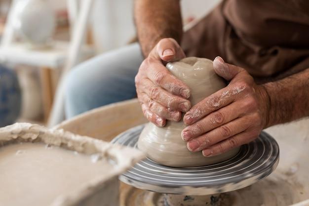 Close-up handen doen aardewerk binnenshuis