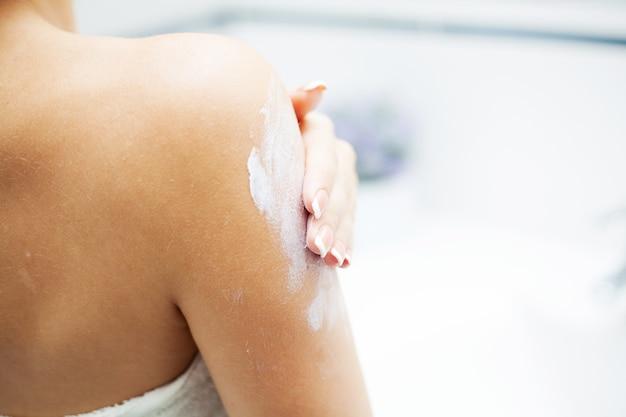 Close-up handen gebruiken verzorgingsproducten in lichte badkamer.
