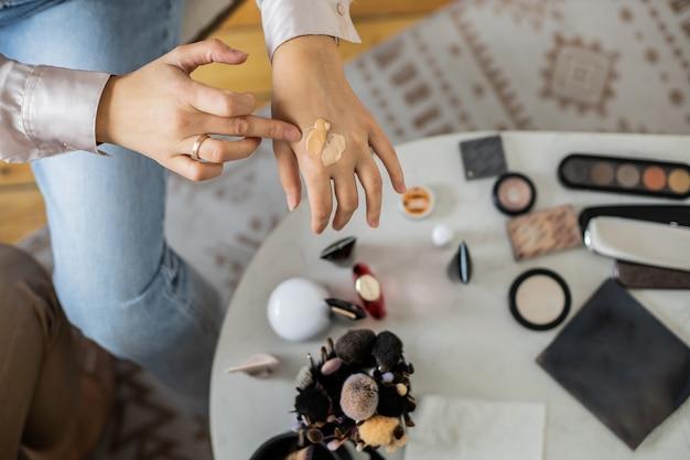 Close-up handen make-up artiest vloeibare foundation toe te passen mengen kleuren huidtint teint
