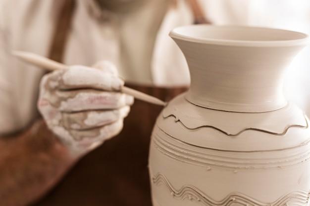 Close-up handen met aardewerk gereedschap