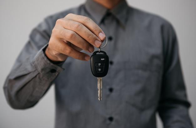 Close-up handen met autosleutels. man met sleutel van auto geven aan agent van verzekering voor verkoop. bedrijfsinvesteringen verzekering autobeslag en autoconcept.