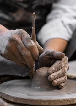 Close-up handen met behulp van aardewerk tool