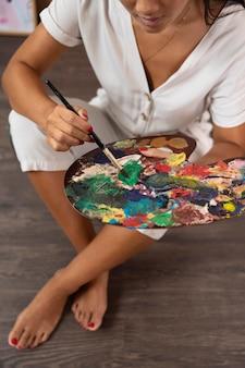 Close-up handen met palet en penseel