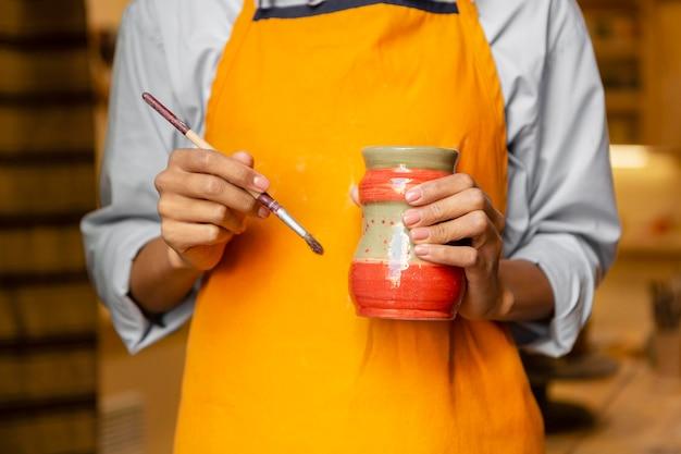 Close-up handen met penseel en aarden pot