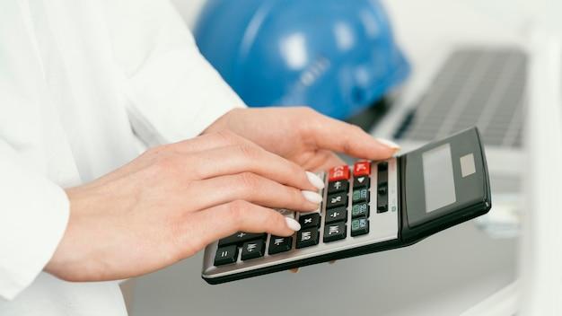 Close-up handen met rekenmachine