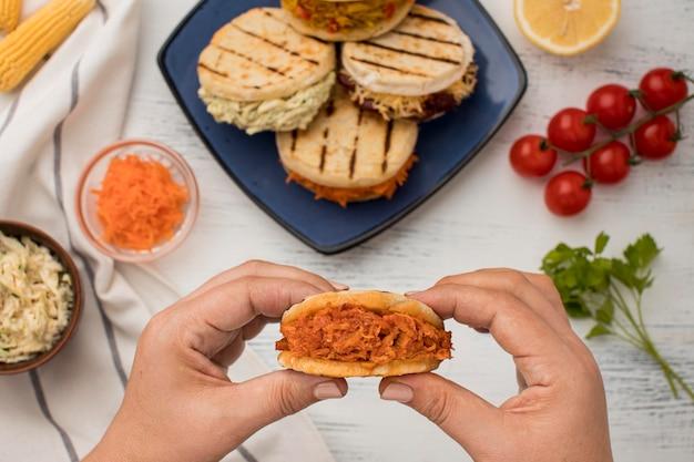 Close-up handen met smakelijke arepa's