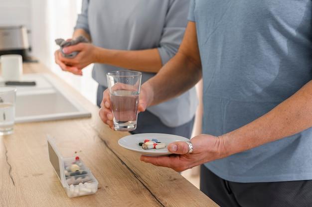 Close-up handen neemt supplementtabletpillen van de pillenorganisator houdt glas water oud vast