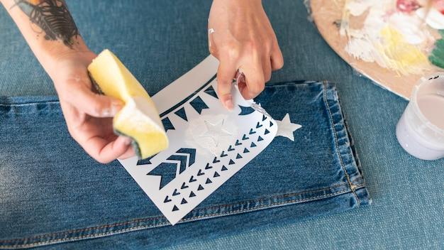Close-up handen schilderij jeans