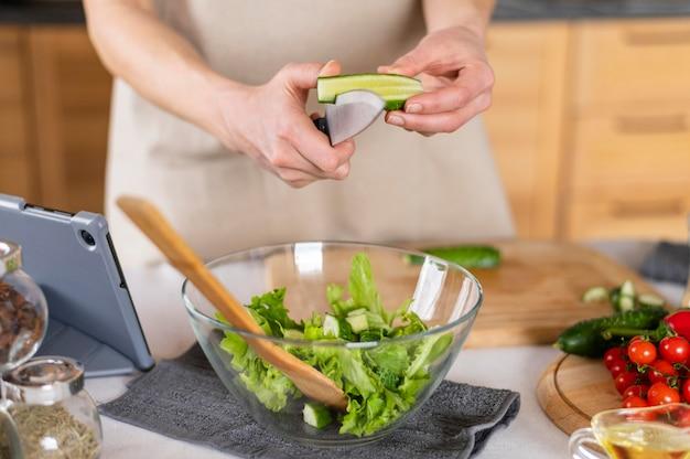 Close-up handen snijden komkommer in keuken
