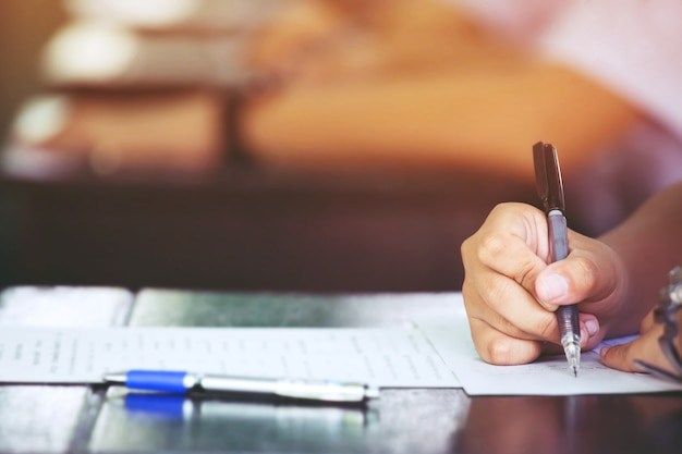 Close-up handen studenten die tests examens examen assessments in de klas afleggen om omhoog te gaan in de laatste