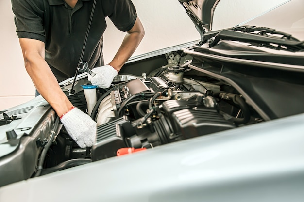 Close-up handen van automonteur die de moersleutel gebruikt om de motor van een auto te onderhouden.