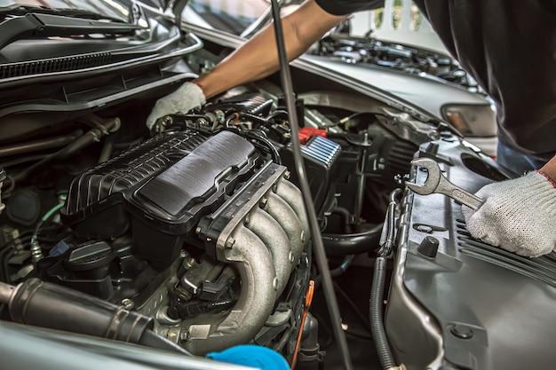 Close-up handen van automonteur gebruiken de moersleutel om automotor te repareren en te onderhouden.