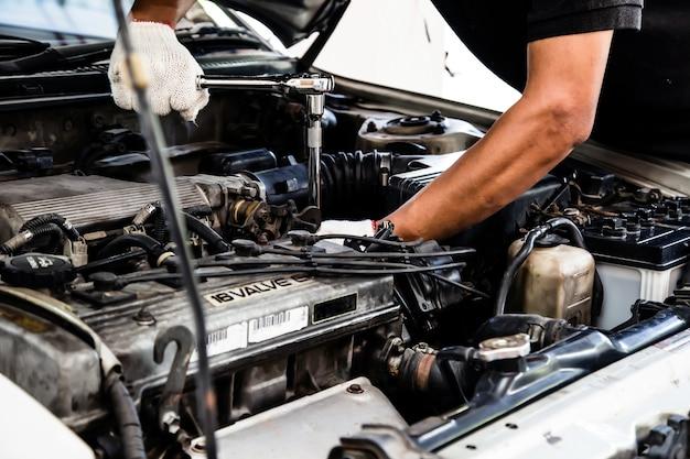Close-up handen van automonteur gebruiken de moersleutel om de motor van een auto in auto auto garage te repareren