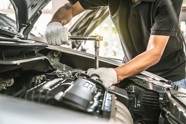 Close-up handen van automonteur gebruiken de moersleutel om de motor van een auto te repareren.