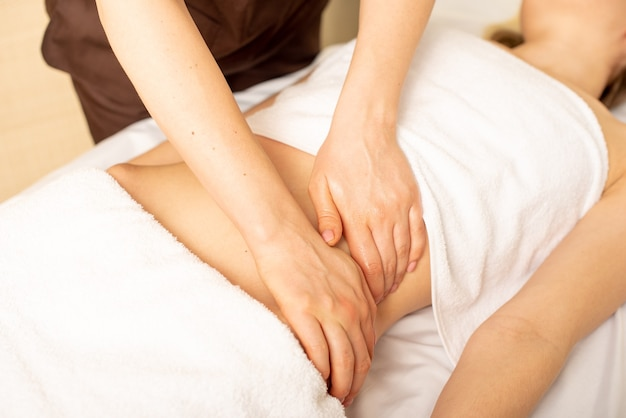 Close-up handen van chiropractor of masseur maken ontspannende massage van maag voor liggende vrouw in kliniek interieur.